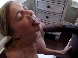 Senior wife is taking a big facial of a black bull